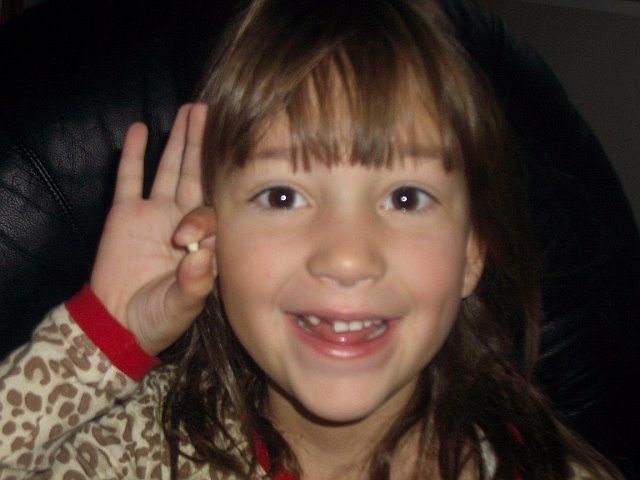 Smiling_girl_holding_up_baby_tooth
